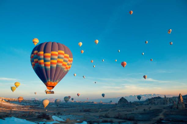 hete lucht ballonnen in cappadocië - aardpiramide stockfoto's en -beelden