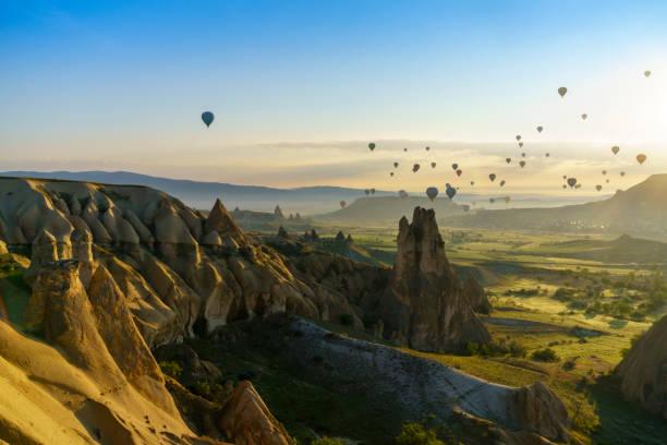hete lucht ballonnen op cappadocia hemel met sunrise - aardpiramide stockfoto's en -beelden