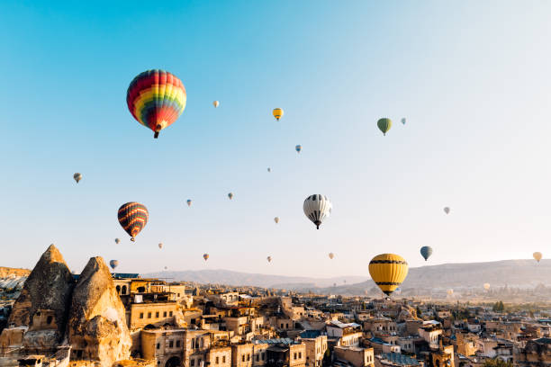 hot air balloons over cappadocia at sunrise,turkey - турция стоковые фото и изображения
