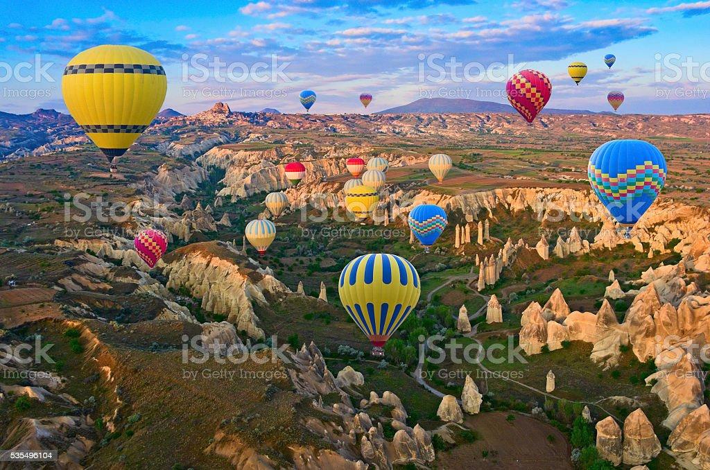 Hot air balloons over mountain landscape in Cappadocia,Turkey. stock photo