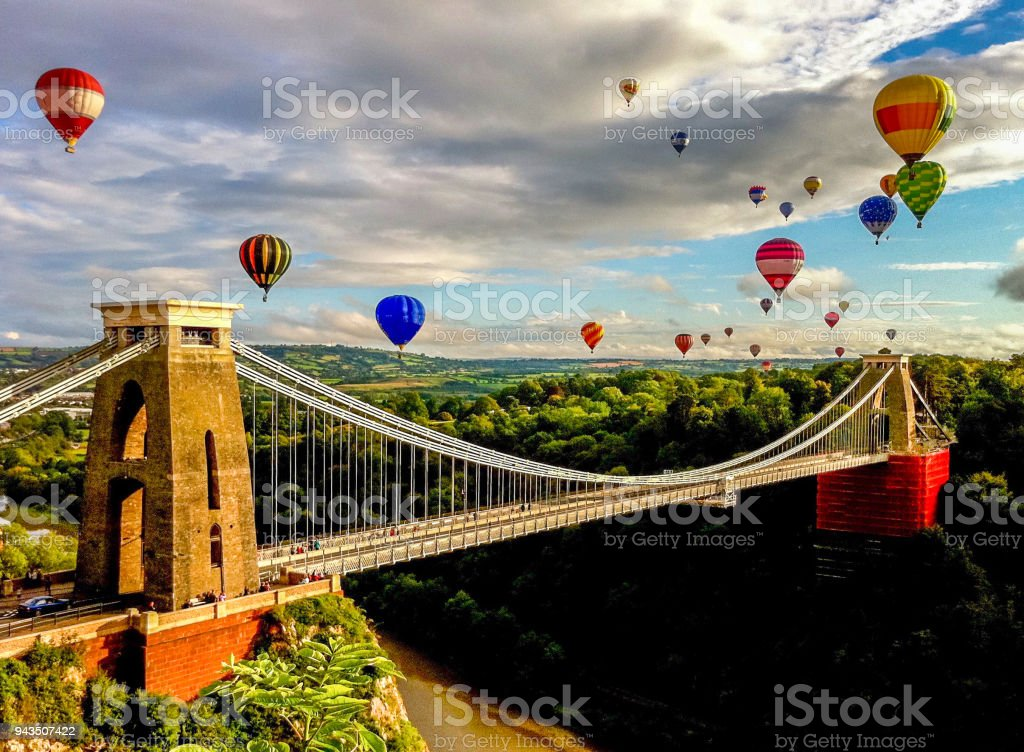 Hot air balloons over suspension bridge in the English countryside stock photo