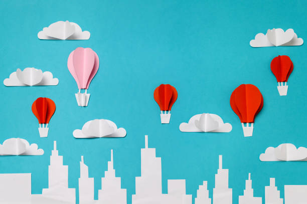 Hot air balloons paper cut objects in the sky above city skyline. Craft paper objects photography for banners/landing pages/backgrounds design with copy space. stock photo