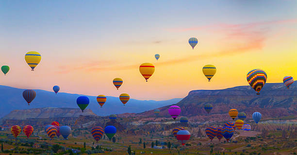 Hot air balloons sunset Cappadocia, Turkey sunset Hot air balloons landing in a mountain Cappadocia Goreme National Park Turkey. tuff stock pictures, royalty-free photos & images