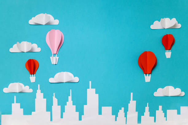 Hot air balloons with clouds above city skyline. Craft paper cut objects photography for banners/landing pages/backgrounds design with copy space. stock photo