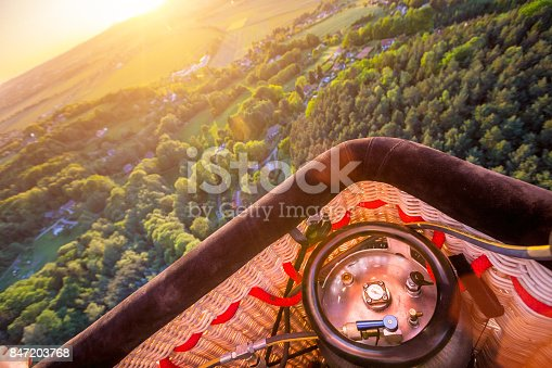 A hot air baloon rising high with dawn sunlight. Unusual perspective view.