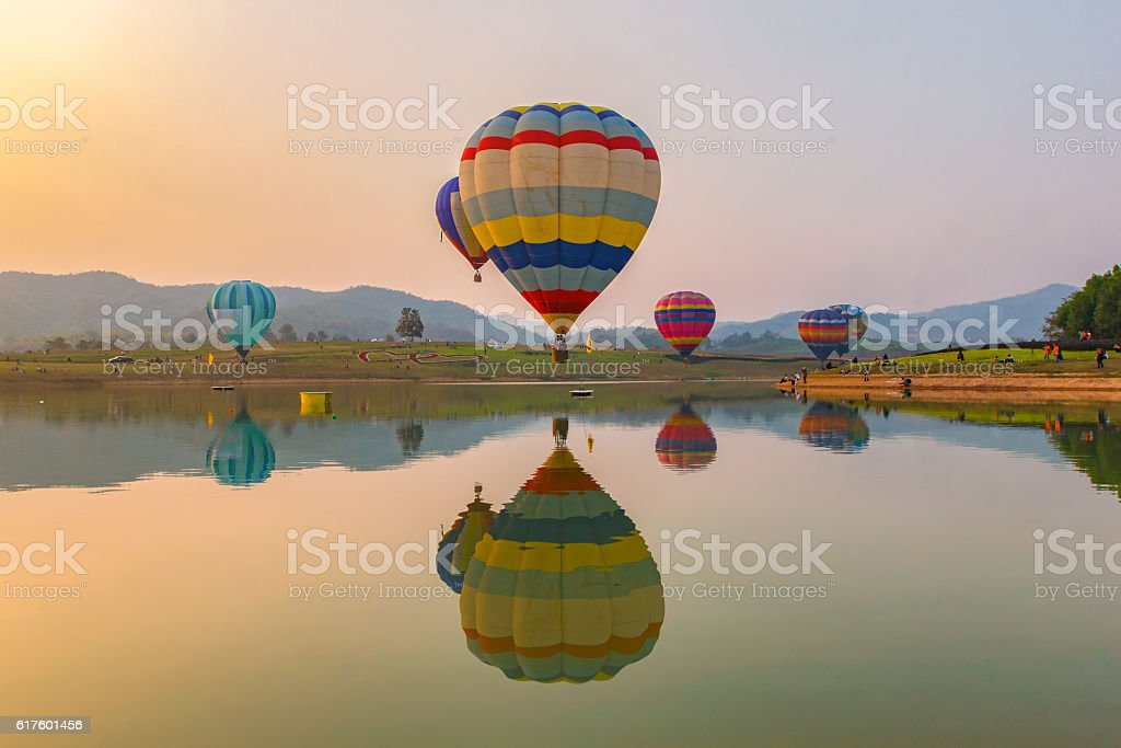 Hot air color balloon over lake with sunset time stock photo