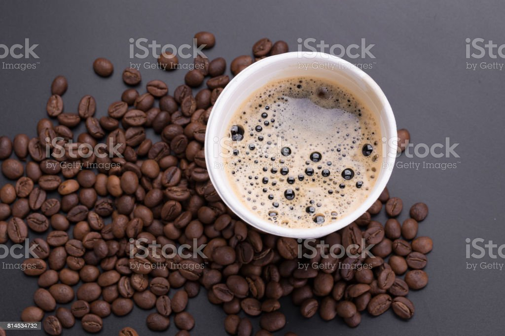 Hot americano coffee in paper cup of coffee and coffee beans on black background stock photo