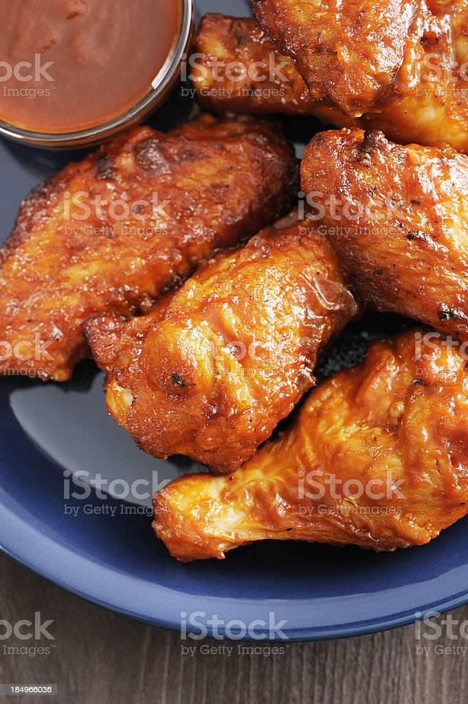 Hot and spicy chicken wings served on a blue plate stock photo
