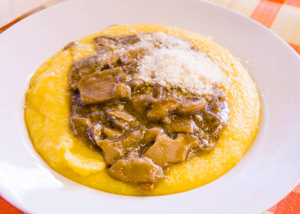 hot and steaming corn polenta topped with mushroom sauce ready for your meal stock photo