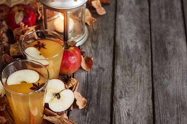 Hot apple cider background Hot apple cider with cinnamon sticks and spices on fall leaves background hot apple cider stock pictures, royalty-free photos & images