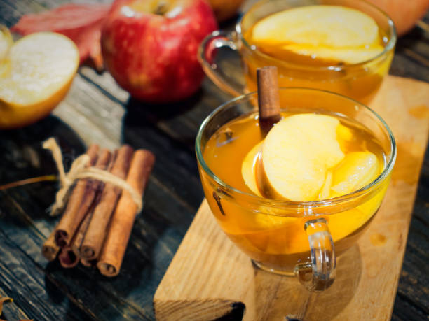Hot apple cider in autumn Two cups of hot apple cider on wooden table with fresh apples, cinnamon and maple leaves hot apple cider stock pictures, royalty-free photos & images
