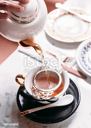 Hot Apple Tea served by pouring from mug through stainless steel tea strainer infuser in porcelain vintage cup.