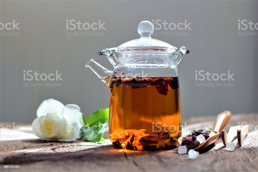 Hot aromatic fruit tea in a glass teapot. Traditional instruments for tea drinking and Chinese tea on a dark and rough wooden table. The concept of tea drinking. Lifestyle wabi sabi. royalty-free stock photo
