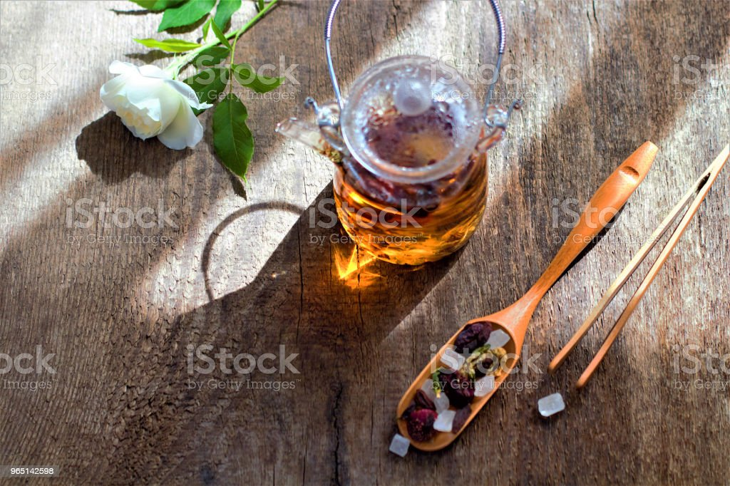 Hot aromatic fruit tea in a glass teapot. Traditional instruments for tea drinking and Chinese tea on a dark and rough wooden table. The concept of tea drinking. Lifestyle wabi sabi. zbiór zdjęć royalty-free