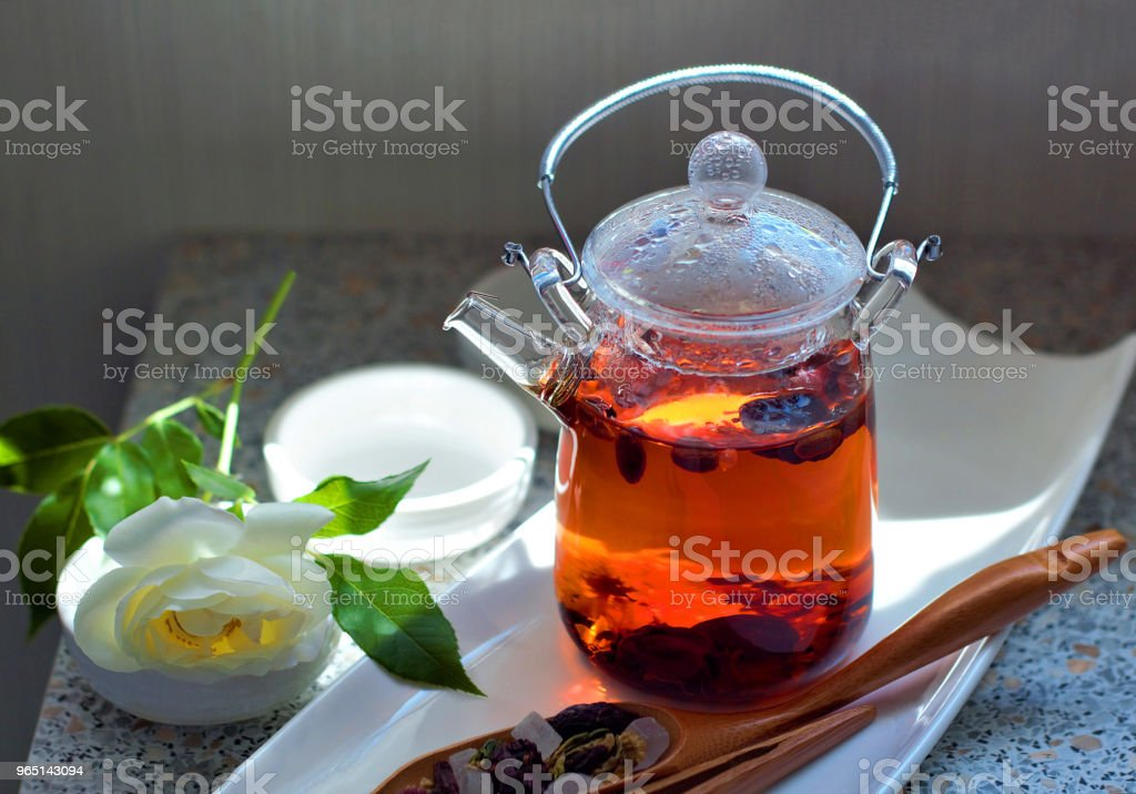 Hot aromatic fruit tea in a glass teapot. Traditional tools for tea drinking and Chinese tea on a light background. The concept of tea drinking. Lifestyle wabi sabi. zbiór zdjęć royalty-free