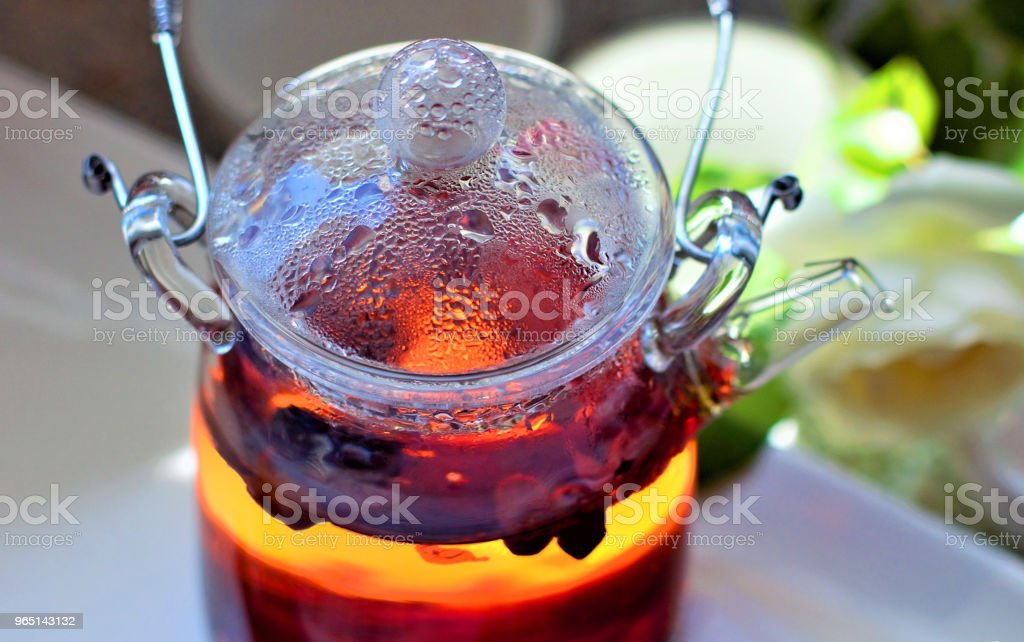 Hot aromatic fruit tea in a glass teapot. Traditional tools for tea drinking and Chinese tea on a light background. The concept of tea drinking. Lifestyle wabi sabi. royalty-free stock photo