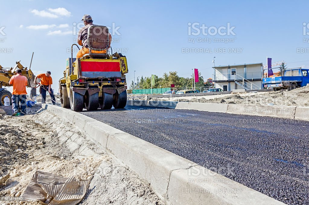 Hot asphalt is spreading with steamroller during road works photo libre de droits