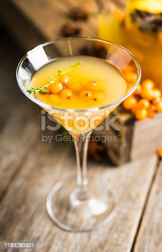 578566044 istock photo Hot autumn cocktail with sea buckthorn and orange juice in martini glass on the rustic background 1183280301