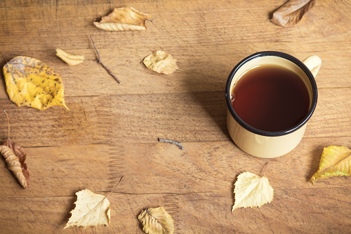 Hot autumn tea and yellow dry leaves
