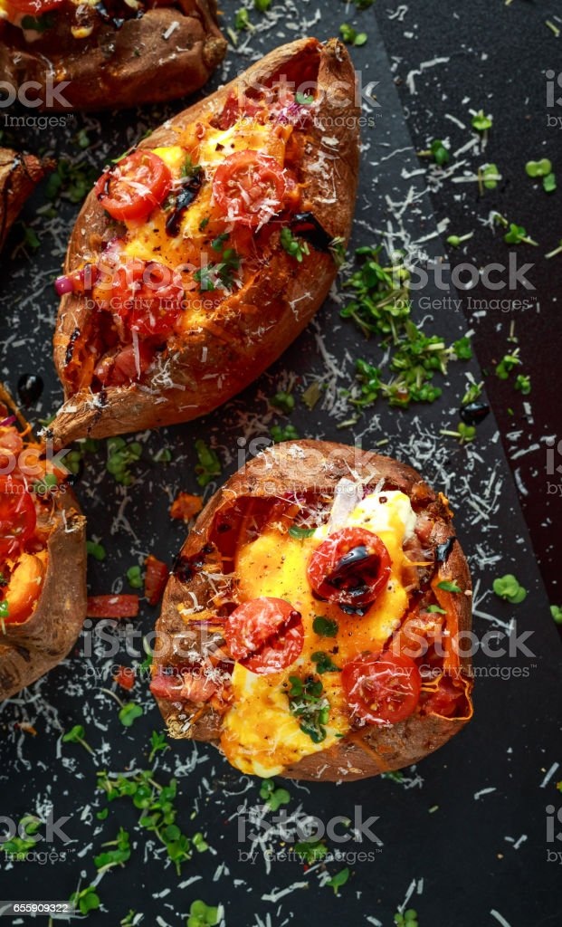 hot baked sweet potato stuffed with bacon, cheddar cheese, cherry tomatoes, balsamic vinegar, cress salad and parmesan sprinkle. Tacco, burrito style. stock photo