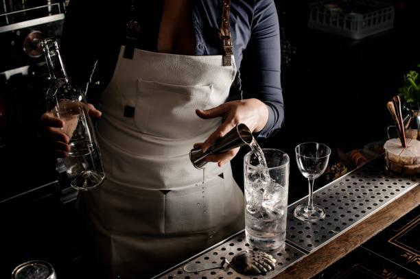 heißen barkeeper frau gießen gin in ein cocktailglas - cocktails mit wodka stock-fotos und bilder