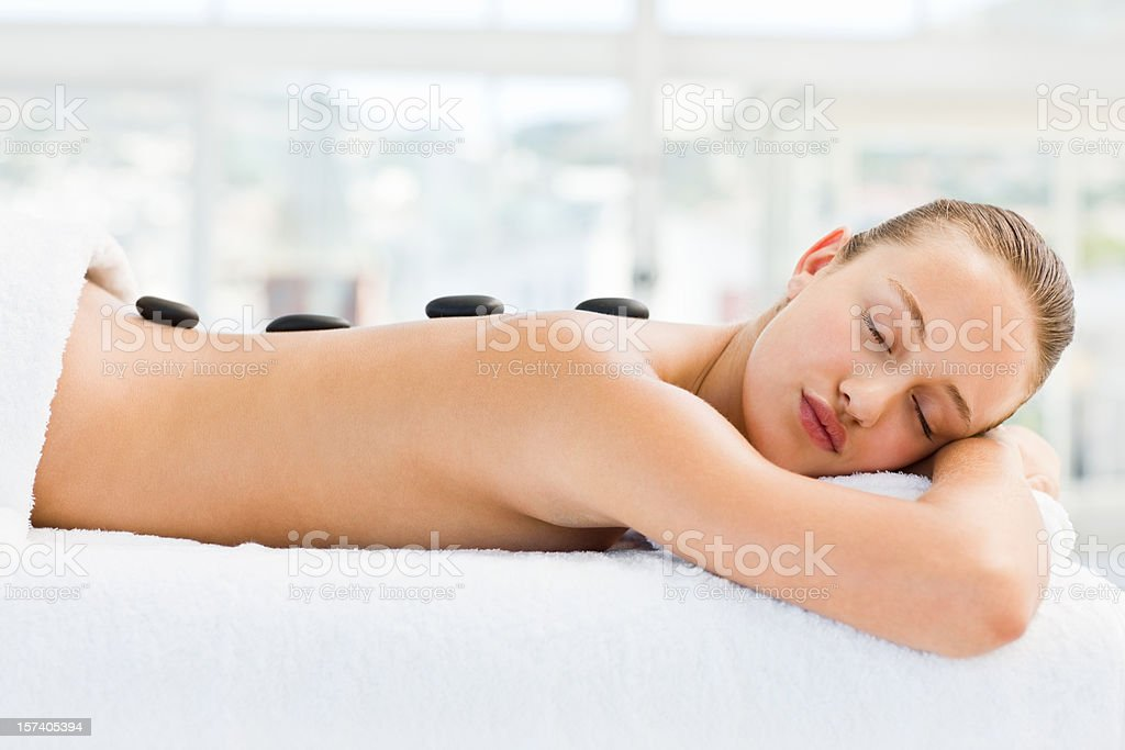 Hot basalt stones applied to woman's back royalty-free stock photo
