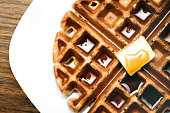 A close up image of a Belgian waffle fresh from the waffle iron and ready to be eaten and covered with maple syrup and butter.  Overhead view of the food on a white plate and wood table.