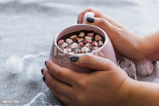 hot chocolate  pink ceramic mug marshmallows and garland  gray knitted background