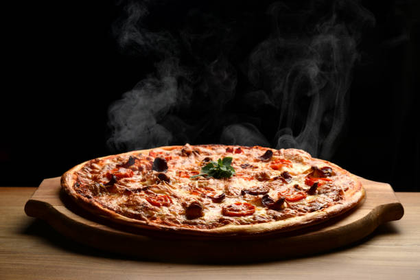 Hot big pepperoni pizza tasty pizza composition with melting cheese bacon tomatoes ham paprika steam smoke Hot big pepperoni pizza tasty pizza composition with melting cheese bacon tomatoes ham paprika steam smoke on black background pizza stock pictures, royalty-free photos & images