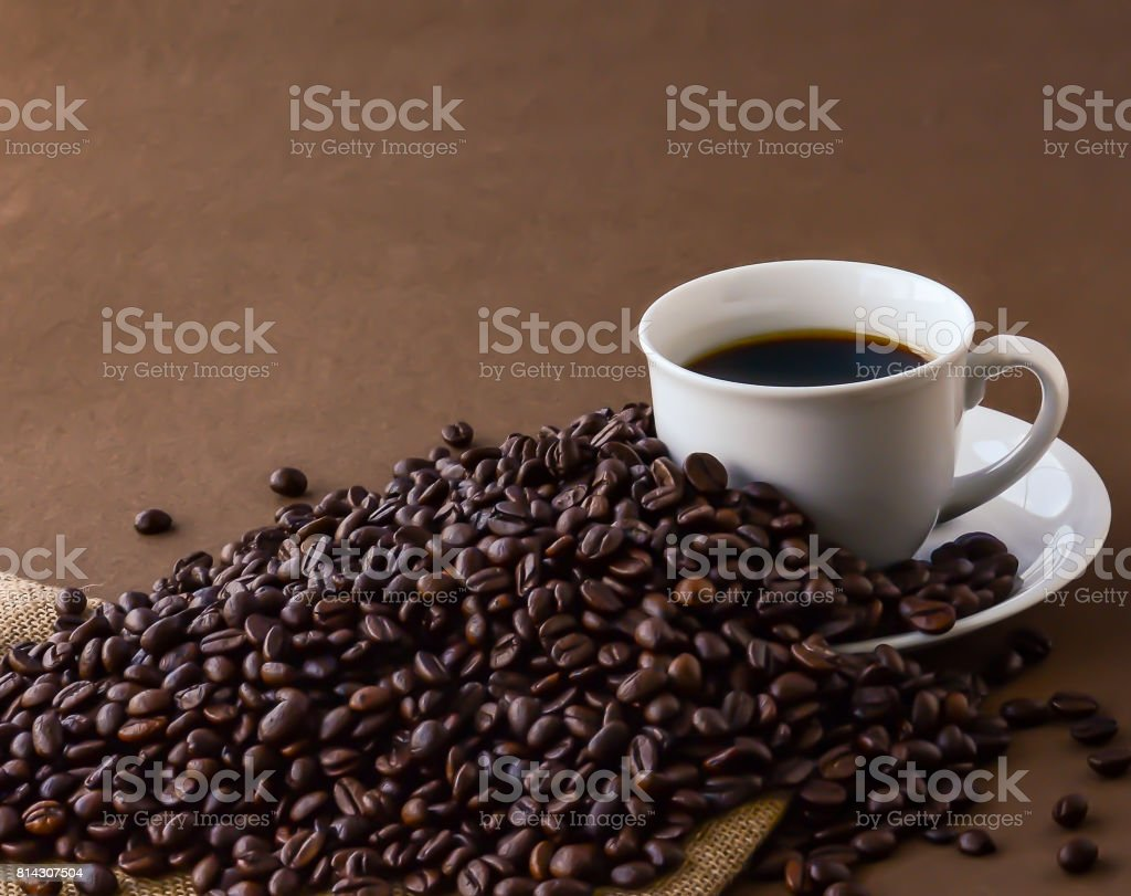 Hot black coffee in a white cup and coffee roast beans. stock photo