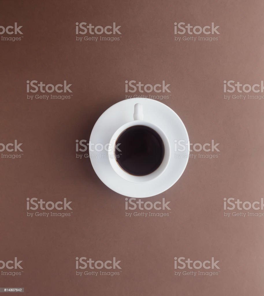 Hot black coffee in a white cup on brown paper in top view. stock photo