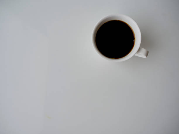 Hot black coffee with smoke in a white cup on a white table stock photo