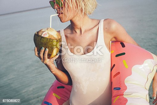 Sexy blonde girl is on vacation on Maldives. She is at the beach, near ocean, standing in shallow water in inflatable donut and drinking from her coconut fruit glass. She is wearing white one piece swimsuit and sunglasses. Her hair is wet and swimsuit also, as she just got out of water. With her left hand she holds donut. It's beautiful and sunny day, and she is really enjoying on her vacation.