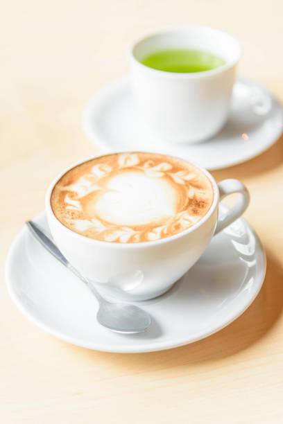 hot cappuccino coffee with green tea on table stock photo