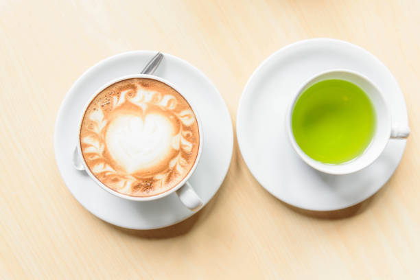 hot cappuccino coffee with green tea on table hot cappuccino coffee with green tea on table greentea stock pictures, royalty-free photos & images
