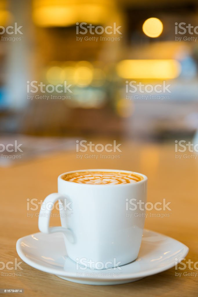 Hot caramel macchiato on wooden table. stock photo