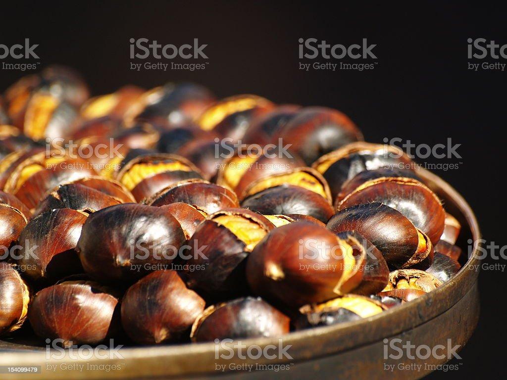 Hot chestnuts on black background. stock photo