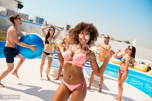 istock Hot mulatto chic with mohito is posing, dancing at the beach pool disco party, enjoying, chilling with friends, they play ball, with huge ribbon blue baloon, at the roof top resort with great view 936185494