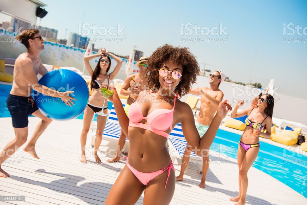 Hot mulatto chic with mohito is posing, dancing at the beach pool disco party, enjoying, chilling with friends, they play ball, with huge ribbon blue baloon, at the roof top resort with great view stock photo