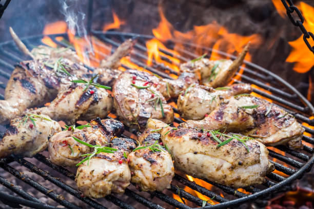 Hot chicken on grill with spices and rosemary stock photo