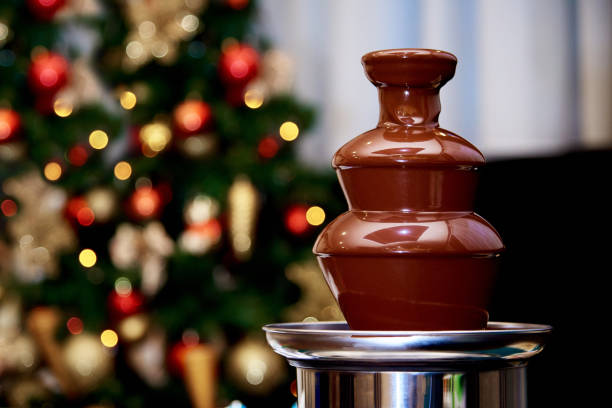 Hot chocolate fountain on the background of the Christmas tree. Hot chocolate fountain on the background of the Christmas tree. chocolate fondue stock pictures, royalty-free photos & images