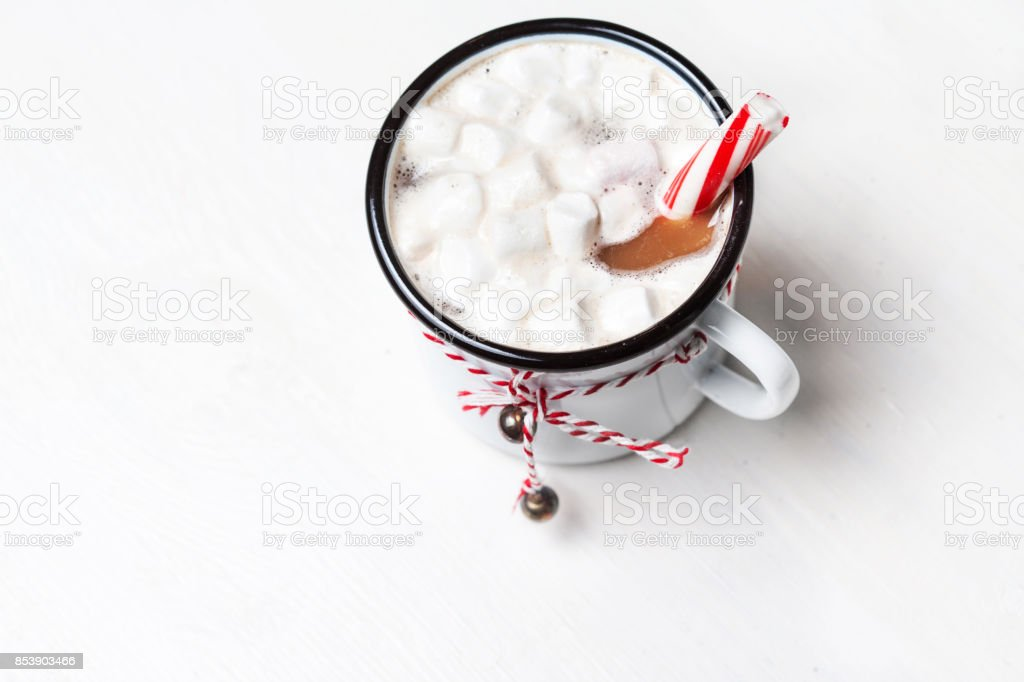 Hot chocolate mug  with marshmallow with sweet red candy striped stick. Vintage mug of winter cocoa with cinnamon stick. Christmas cozy home concept stock photo