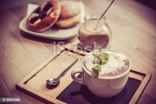 Hot chocolate with bread, mint on top, vintage  photo in coffee shop