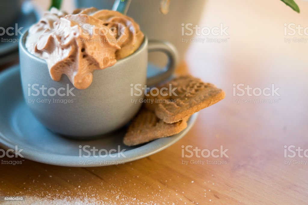 hot chocolate with brown whipped cream against wooden background stock photo