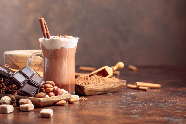 Hot chocolate with cocoa powder, cream, cinnamon, chocolate pieces and other ingredients on a brown table. stock photo