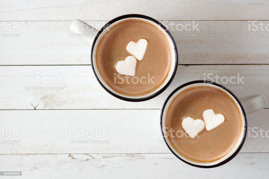 Hot chocolate with heart marshmallows over white wood stock photo