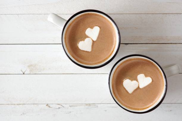 hot chocolate with heart marshmallows over white wood - hot chocolate stock photos and pictures