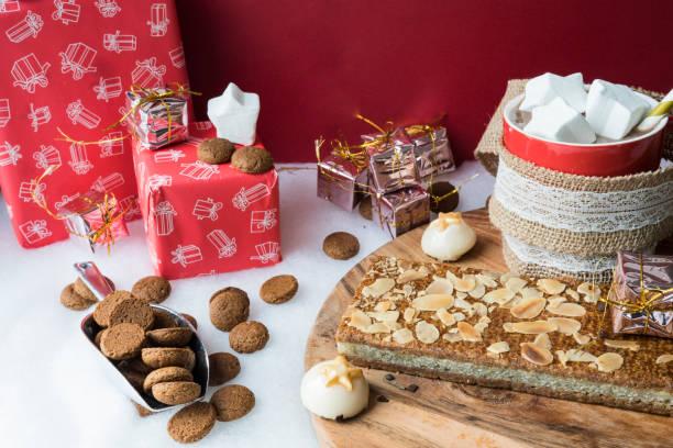 warme chocolademelk met marshmallows, kruidnoten, pop, voor nederlandse evenement sinterklaas, tegen rode achtergrond - cadeau sinterklaas stockfoto's en -beelden