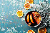Hot christmas mulled wine or gluhwein with spices and orange slices on vintage teal table top view. Traditional drink on winter holiday. Copy space for design and data.