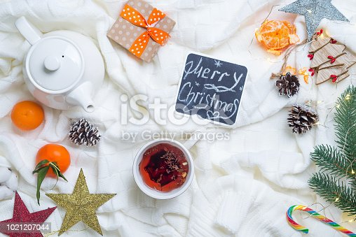 859424970istockphoto hot christmas tea with candy cane against decorations, gift boxes, ribbon and mandarin on knitted white warm blanket. Xmas concept. 1021207044